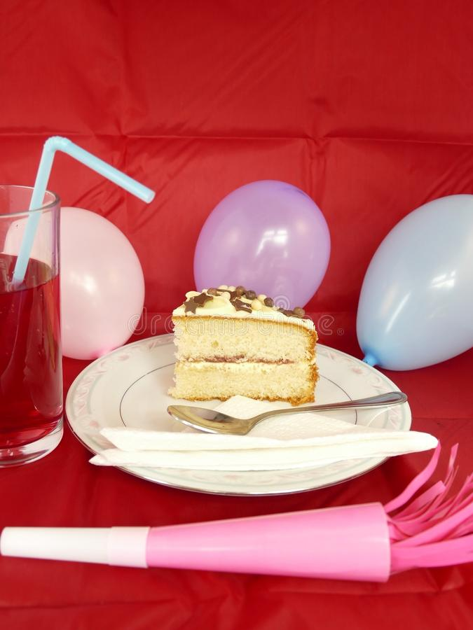 Birthday party food time. Scrumptious birthday cake balloons squash drink with straw and a party horn,set in a red background stock photos