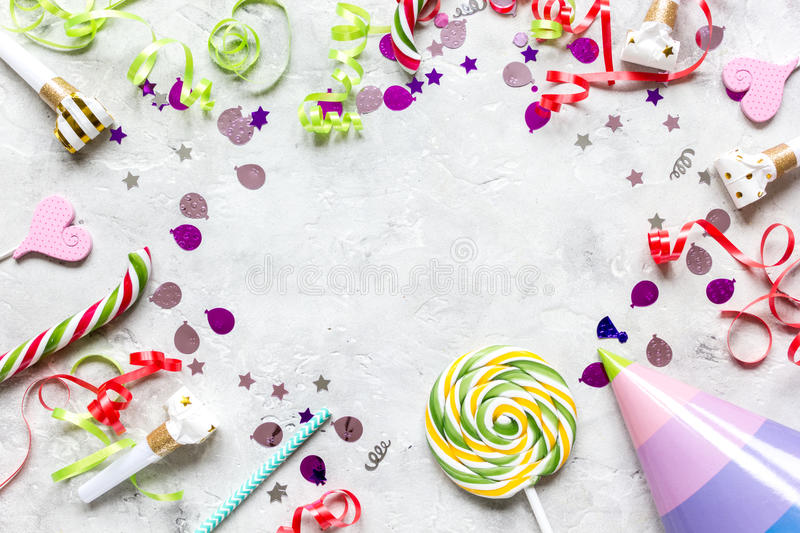 Birthday party frame with hat for mock-up on stone background top view. Birthday party colorful frame for mock-up with hat and confetti on stone background top royalty free stock image