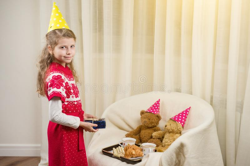 Birthday party, Girl kid in a festive hat playing with teddy bears. Birthday party, Girl kid in festive hat playing with teddy bears royalty free stock photography