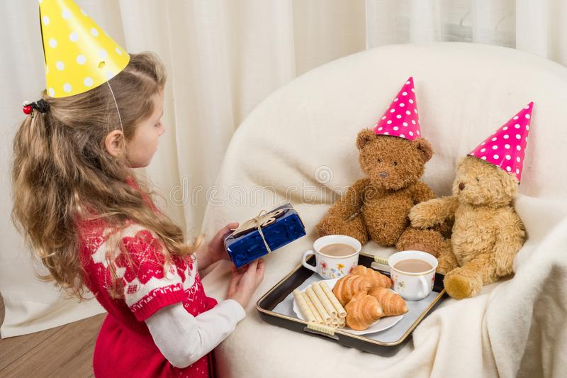 Birthday party, Girl kid in a festive hat playing with teddy bears. Birthday party, Girl kid in festive hat playing with teddy bears stock photo