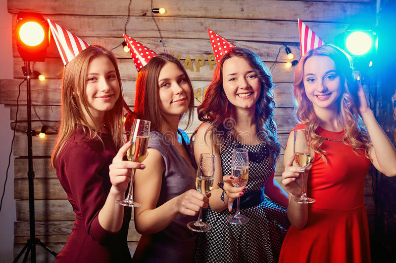 Birthday party girlfriends. Beautiful girl in a cap with glasses royalty free stock photos