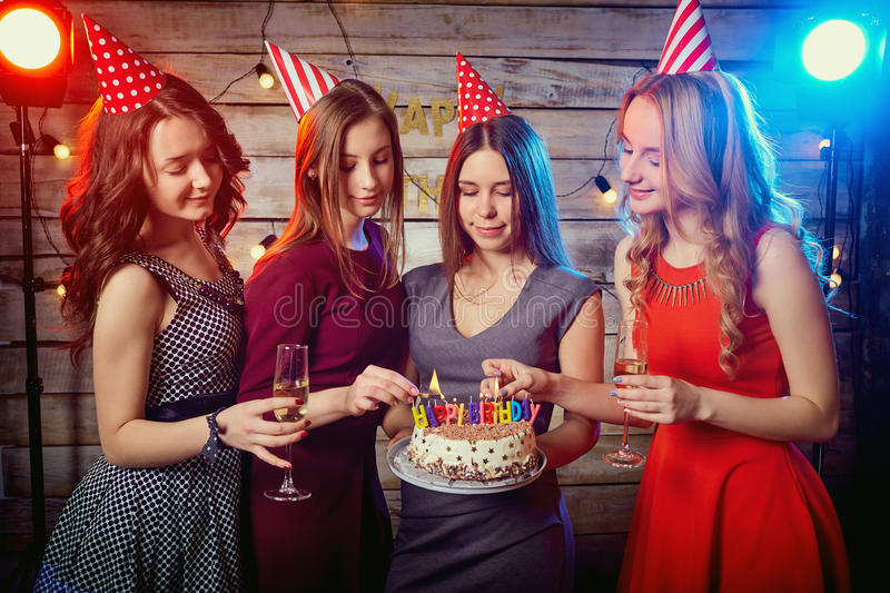 Birthday party girlfriends. Women light candles on the cake with stock photo