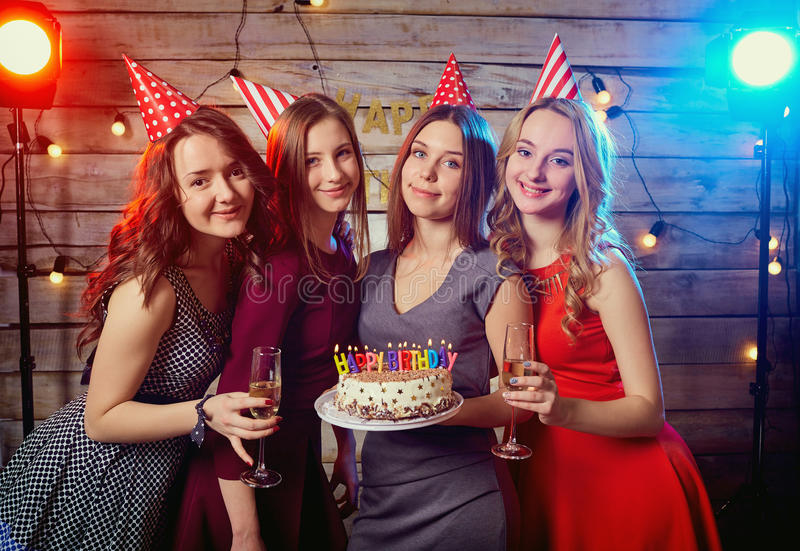 Birthday party girlfriends. Women light candles on the cake with royalty free stock images