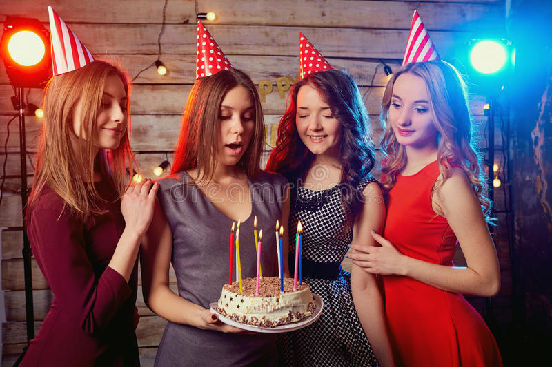 Birthday party girlfriends. Women light candles on the cake with stock photography