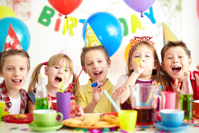 At birthday party. Group of adorable kids having fun by festive table at birthday party stock images