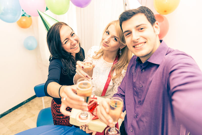 Birthday party. Group of friends celebrating birthday - Young men holding camera and taking a picture with camera while at his girlfriend's party - Young stock image