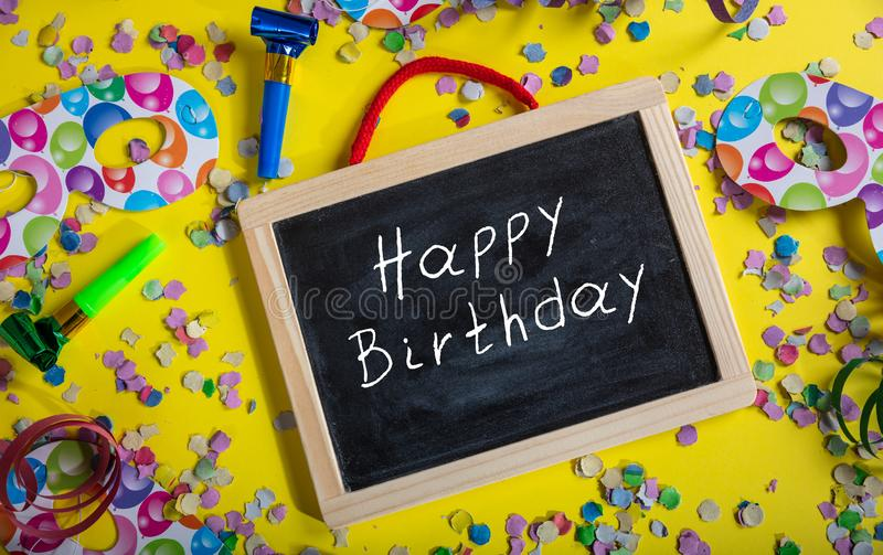 Birthday party. Happy birthday text on a blackboard, confetti and serpentines on bright yellow background royalty free stock images