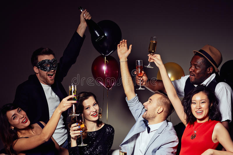 Birthday Party at Home. Having birthday party at home: cheerful friends looking at camera with toothy smiles while clinking champagne flutes together, colorful stock images
