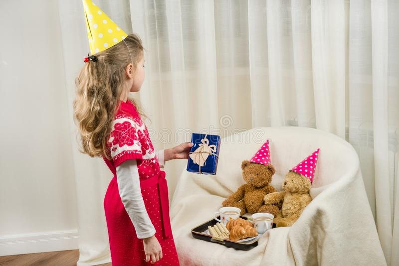 Birthday party, kid in festive hat playing with teddy bears. Birthday party, Girl kid in festive hat playing with teddy bears royalty free stock photography