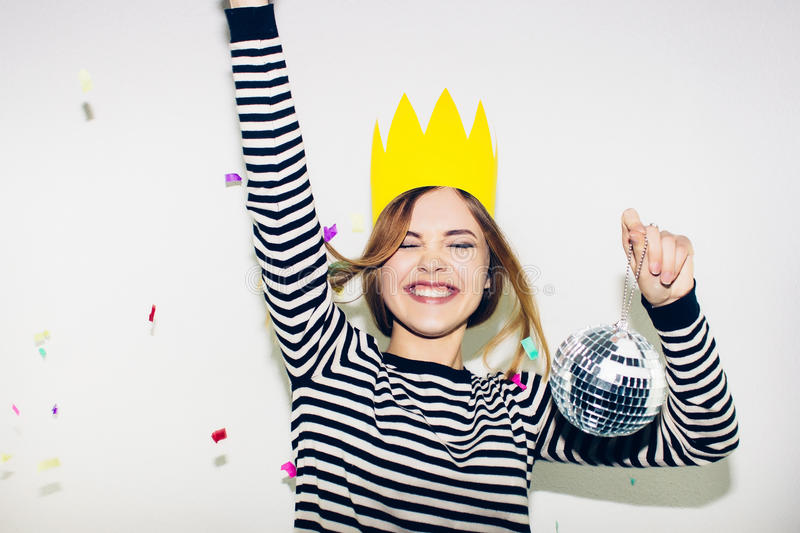 Birthday party, new year carnival. Young smiling woman on white background celebrating brightful event, wears stripped. Birthday party, new year carnival. Young royalty free stock images