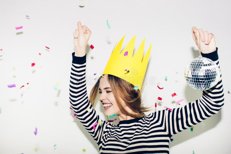 Birthday party, new year carnival. Young smiling woman on white background celebrating brightful event, wears stripped. Birthday party, new year carnival. Young royalty free stock photo