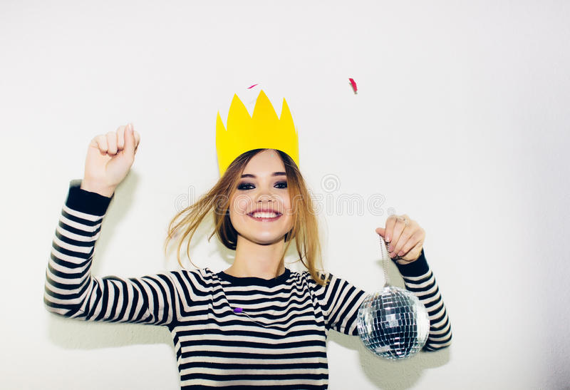 Birthday party, new year carnival. Young smiling woman on white background celebrating brightful event, wears stripped stock image