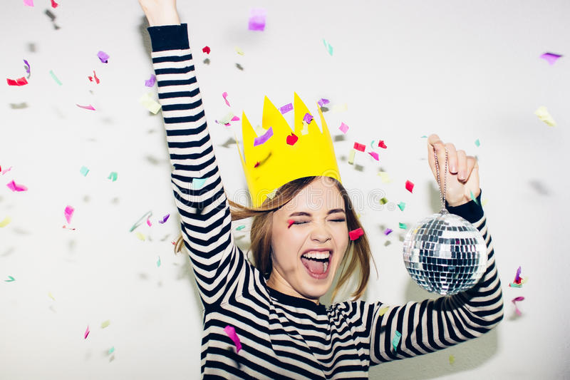Birthday party, new year carnival. Young smiling woman on white background celebrating brightful event, wears stripped stock photography