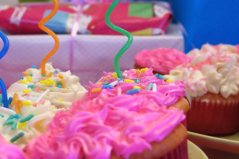Birthday Party Pink and White Cupcakes. Curly Straws Piercing the Decorated Frosting on Pink and White Cupcakes with Wrapped Gifts in the Background royalty free stock image