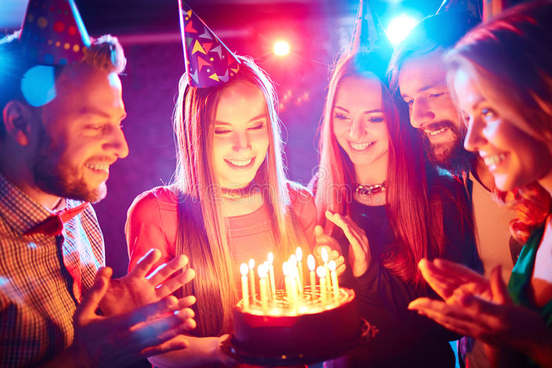 Birthday party. Pretty girl with birthday cake and her friends looking at burning candles at party royalty free stock image
