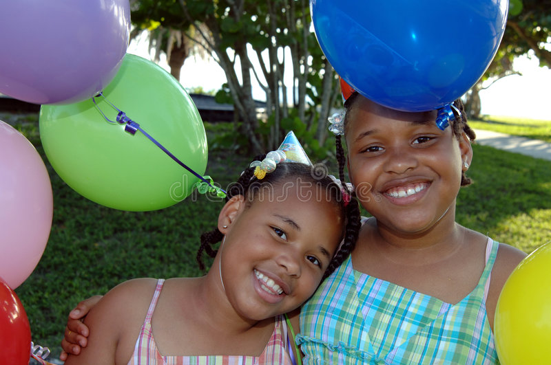 Birthday party sisters. Two african american sisters with balloons at a birthday party royalty free stock photo