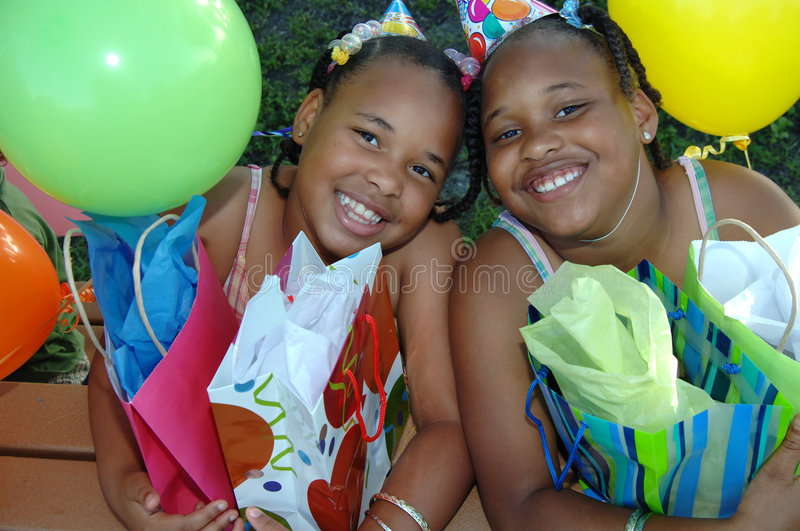Birthday party sisters. Two african american sisters at a birthday party with gifts royalty free stock photo