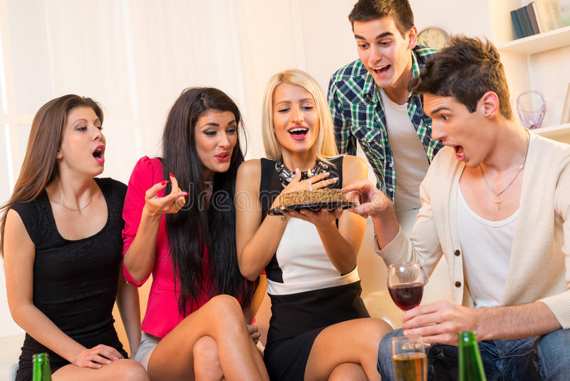 Birthday Party. A small group of young people at a birthday party, sitting on the couch, with cheerful expressions on the faces looking at birthday cake in the royalty free stock photos