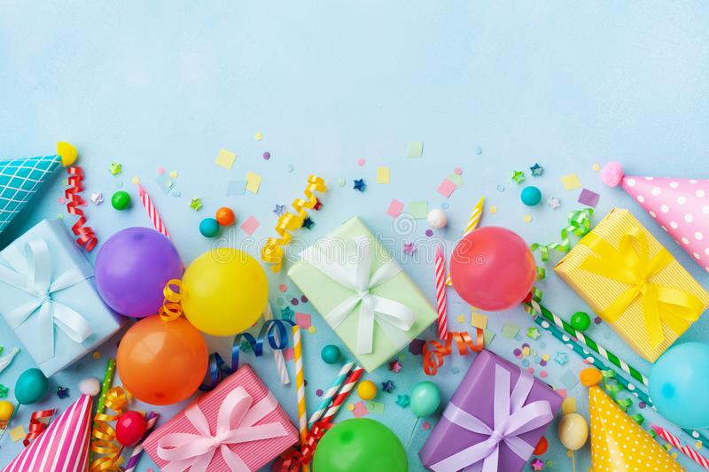 Birthday party table with balloons, gift or present boxes, confetti and holiday supplies. Top view. Birthday party table with balloons, gift or present boxes royalty free stock photography