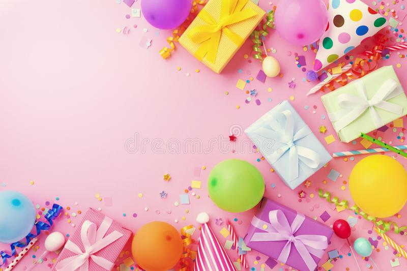 Birthday party table with balloons, gift or present boxes, confetti and holiday supplies. Top view.  royalty free stock photography