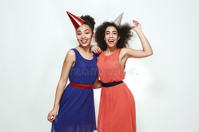 Birthday party! Two cute and young afro american women wearing summer dresses and party hats celebrating a birthday royalty free stock photography