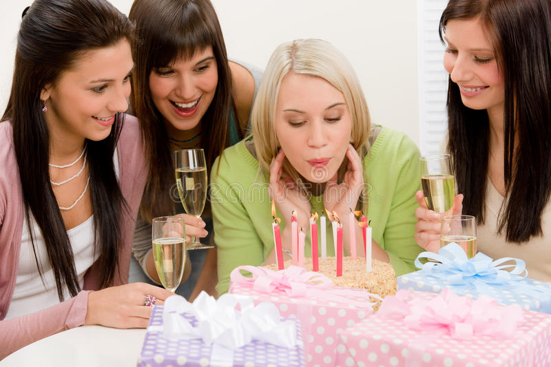 Birthday party - woman blowing candle on cake. Champagne, presents stock images