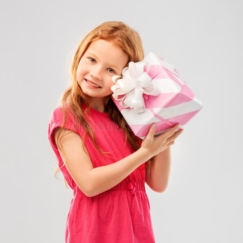 Lovely red haired girl with birthday gift. Birthday and people concept - lovely red haired girl with gift box over grey background stock image