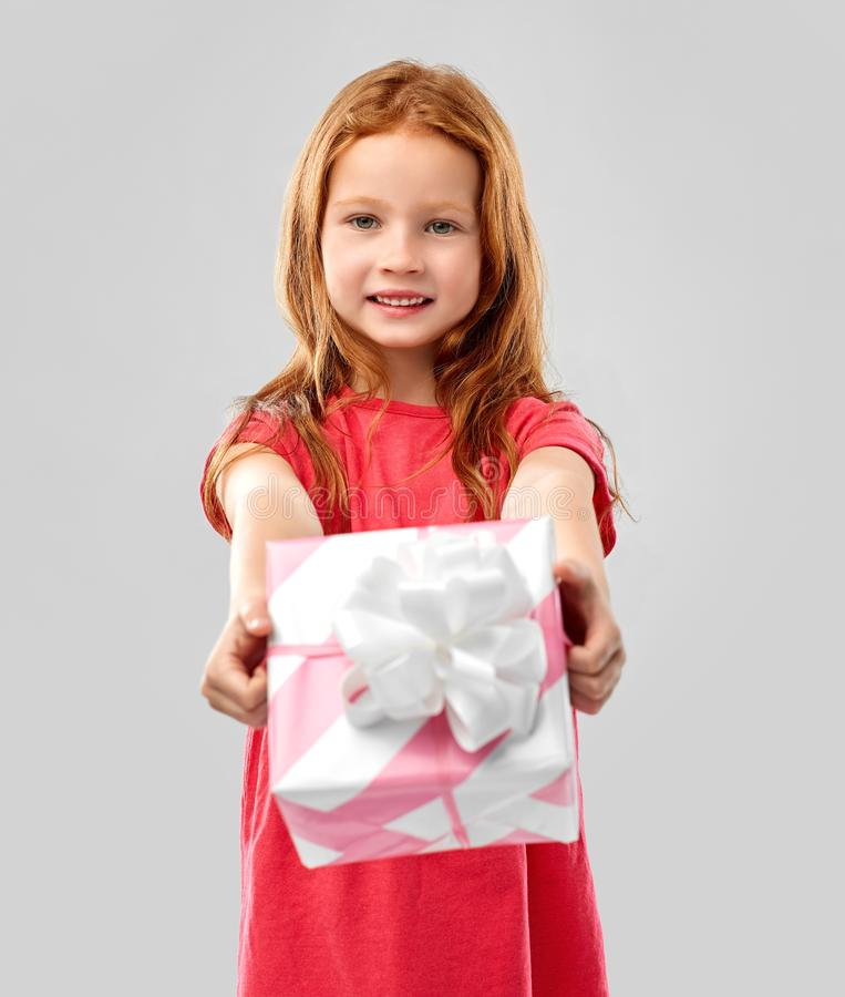 Lovely red haired girl with birthday gift. Birthday and people concept - lovely red haired girl with gift box over grey background royalty free stock images