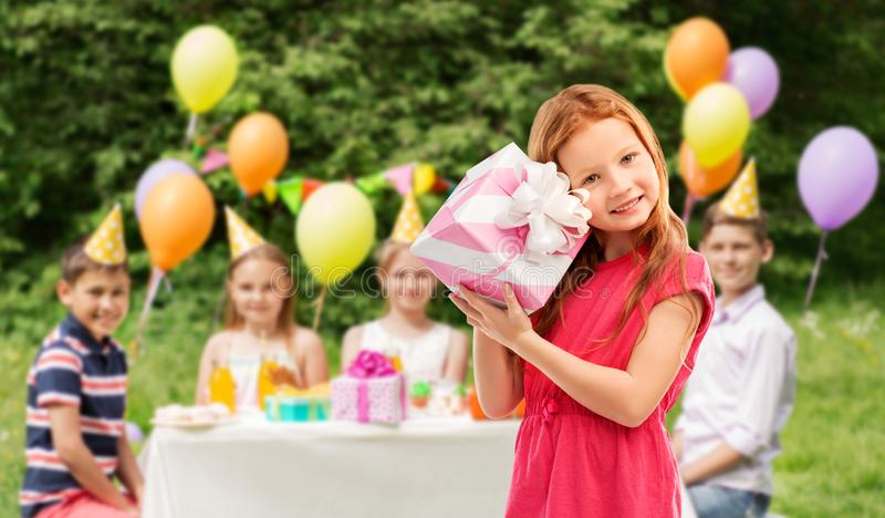 Lovely red haired girl with birthday gift at party. Birthday and people concept - lovely red haired girl with gift box over party at summer park royalty free stock image