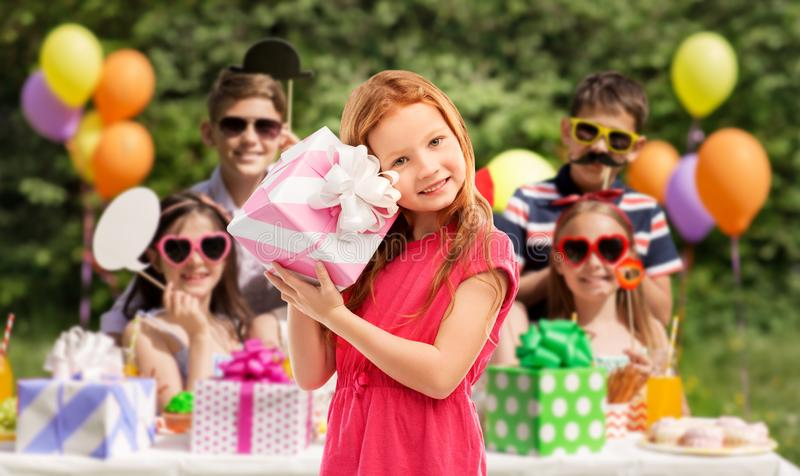 Lovely red haired girl with birthday gift at party. Birthday and people concept - lovely red haired girl with gift box over party at summer park stock images