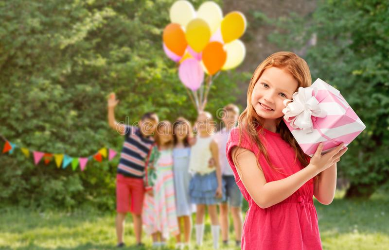 Lovely red haired girl with birthday gift at party. Birthday and people concept - lovely red haired girl with gift box over party at summer park stock photography