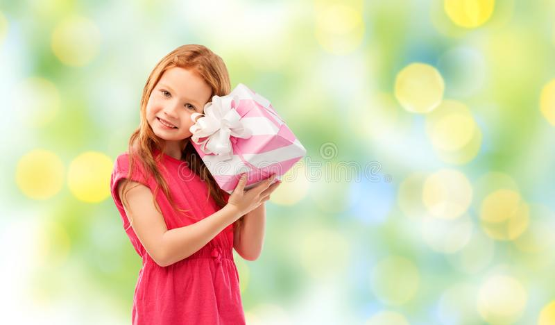 Lovely red haired girl with birthday gift. Birthday and people concept - lovely red haired girl with gift box over summer green lights background stock photos