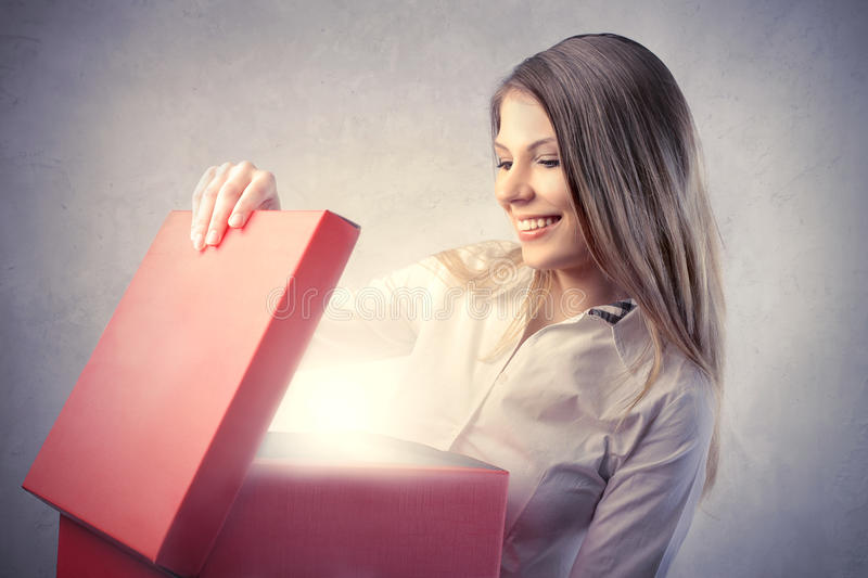 Birthday present. Smiling beautiful woman opening a birthday gift stock images