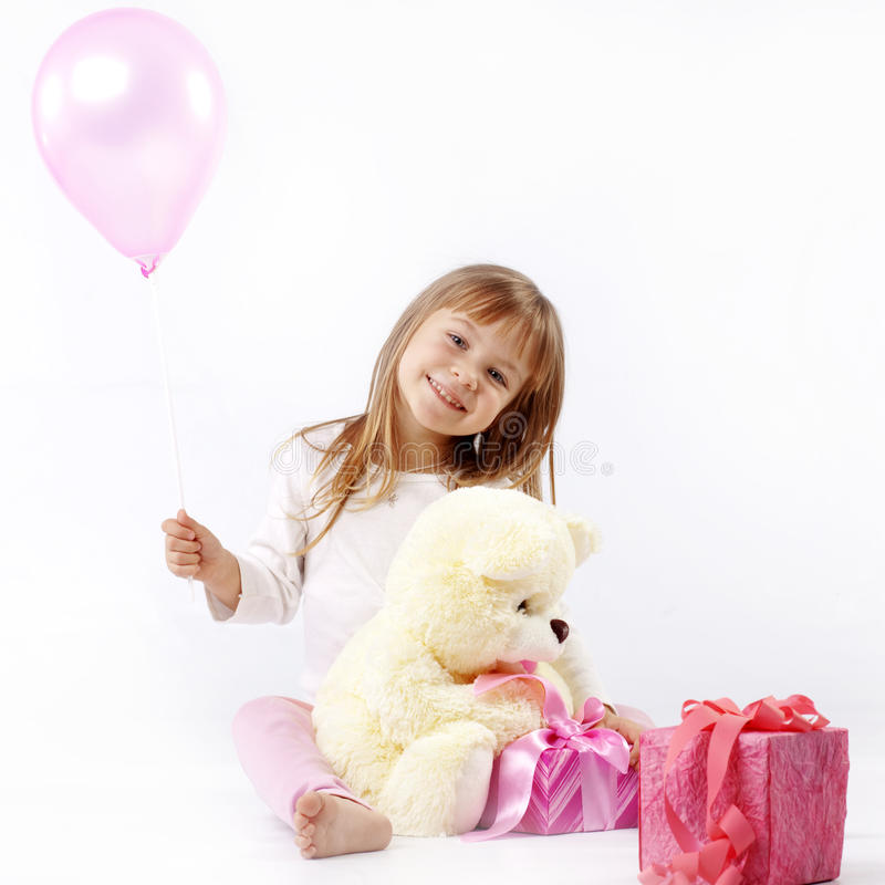 Birthday presents. Sweet little girl is giving presents in her birthday stock image