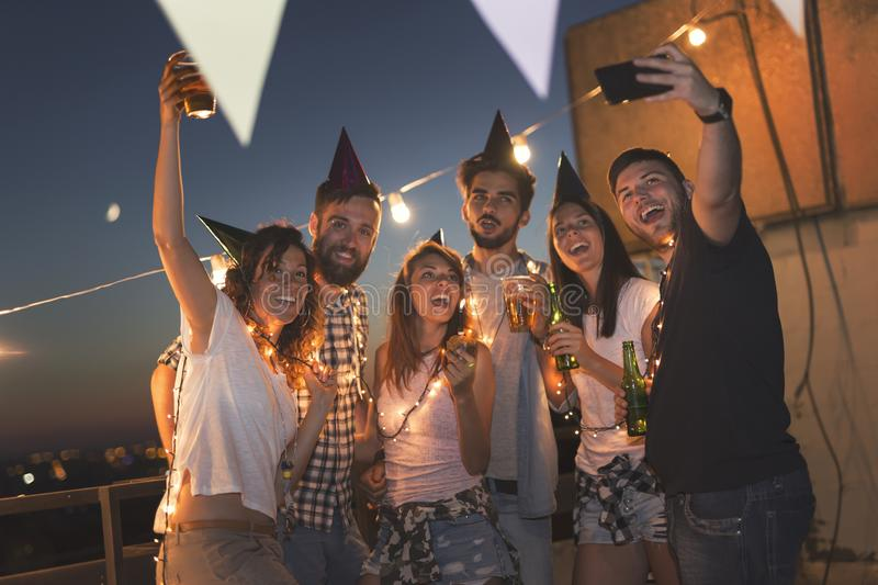 Birthday selfie. Group of young friends having a birthday party at a building rooftop, singing a song, blowing a candle and taking a selfie. Focus on people on stock image