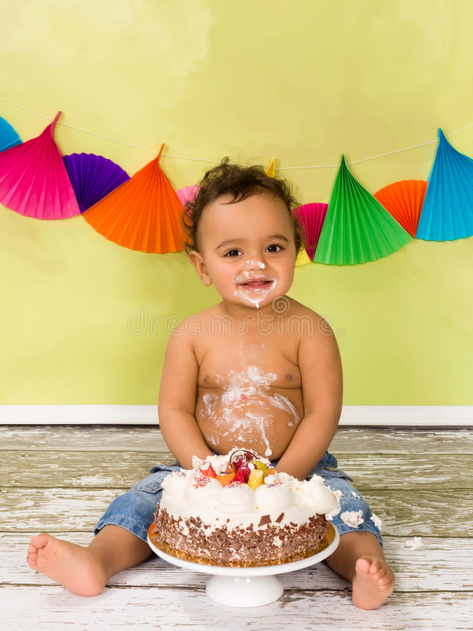 Birthday smile. Adorable african baby during a cake smash on his first birthday royalty free stock photography