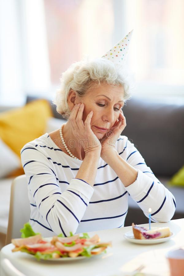 Birthday in solitude. Sad lonely senior lay with gray curly hair sitting at table and looking at cake slice while celebrating birthday in solitude stock photo