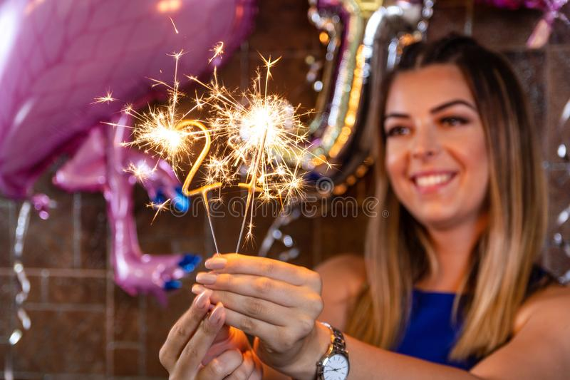 Birthday sparkler burning in hand of a blurred woman in a decorated restaurant stock photos