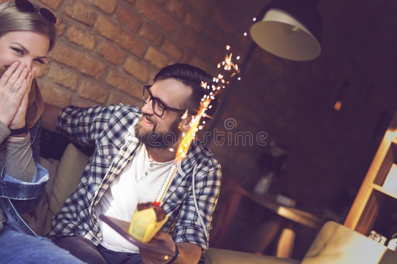 Birthday surprise. Young couple in love sitting in a cafe, boyfriend surprises his girlfriend with a fireworks birthday muffin royalty free stock images