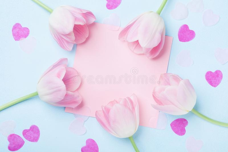 Birthday or wedding mockup with pink paper list, hearts and tulip flowers on blue background top view. Beautiful woman day card. royalty free stock photography