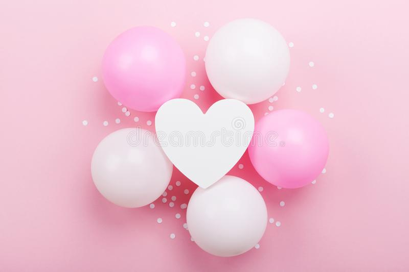 Birthday or wedding mockup with white heart shape, confetti and pastel balloons on pink table top view. Flat lay composition. Birthday or wedding mockup with royalty free stock images