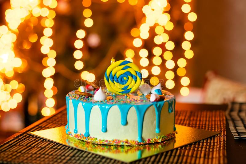 Birthday white cake with sweets and candle for little baby boy and decorations for cake smash royalty free stock image