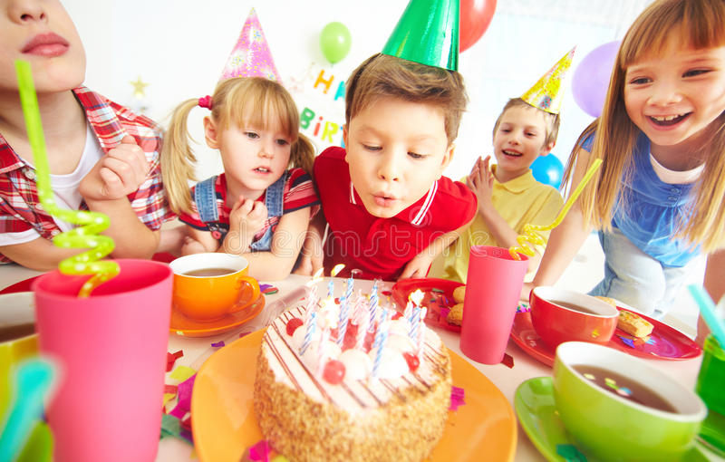 Birthday wish. Group of adorable kids gathered around birthday cake with candles royalty free stock image