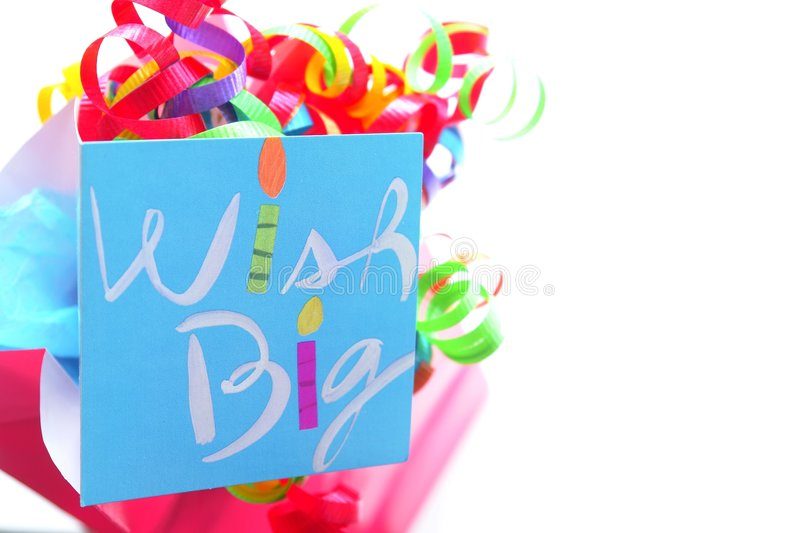Birthday Wishes. Colorful pink gift bag with bright ribbon and a birthday card stock photo