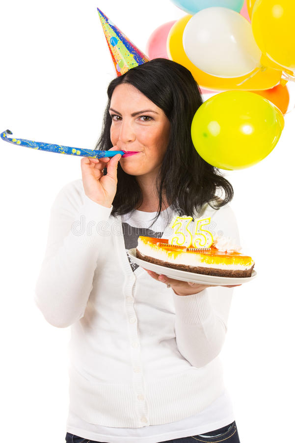 Birthday woman blowing into party horn blower. Woman celebrate her birthday with party hat,balloons,cake and blowing into a horn blower against white background stock photos