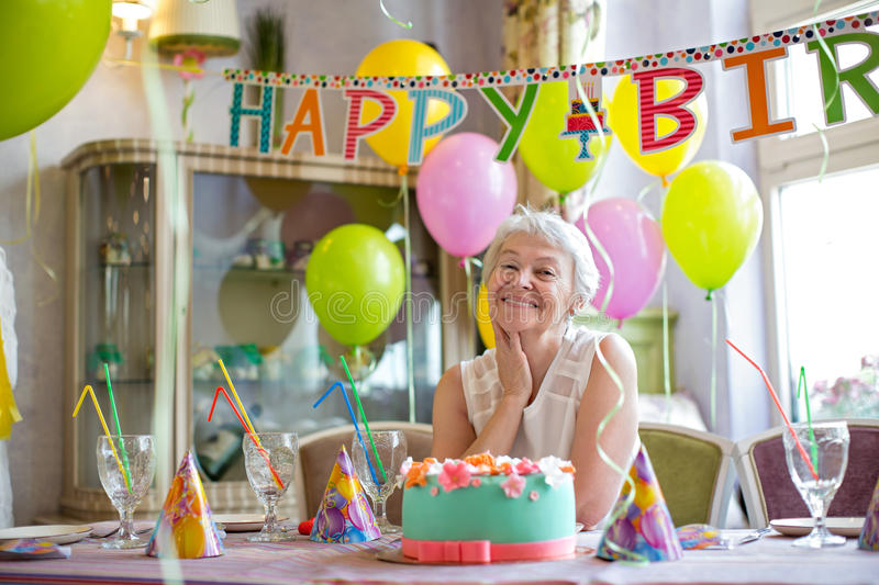 Birthday woman at home. Happy elderly woman at a birthday party royalty free stock image