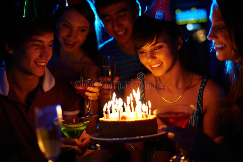 Birthday wonder. Portrait of joyful girl looking at birthday cake surrounded by friends at party stock photos