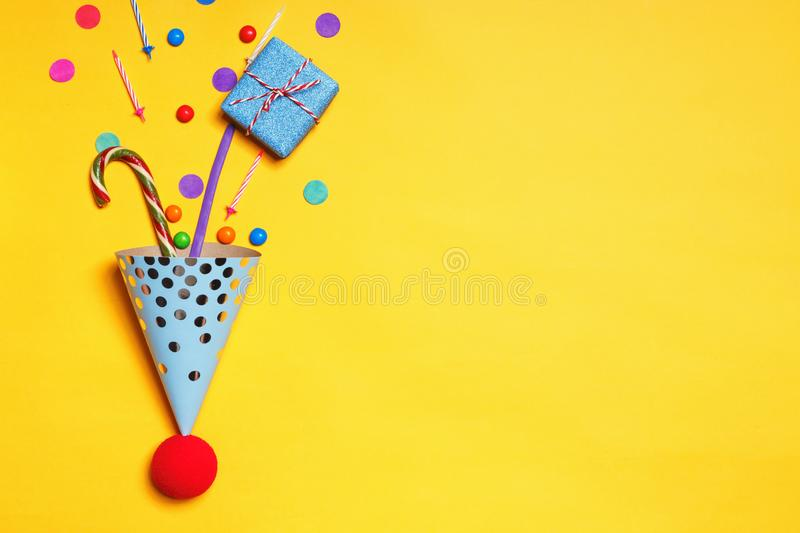 Birthday yellow background with party caps gifts confetti candy candles for a cake with copy space royalty free stock images