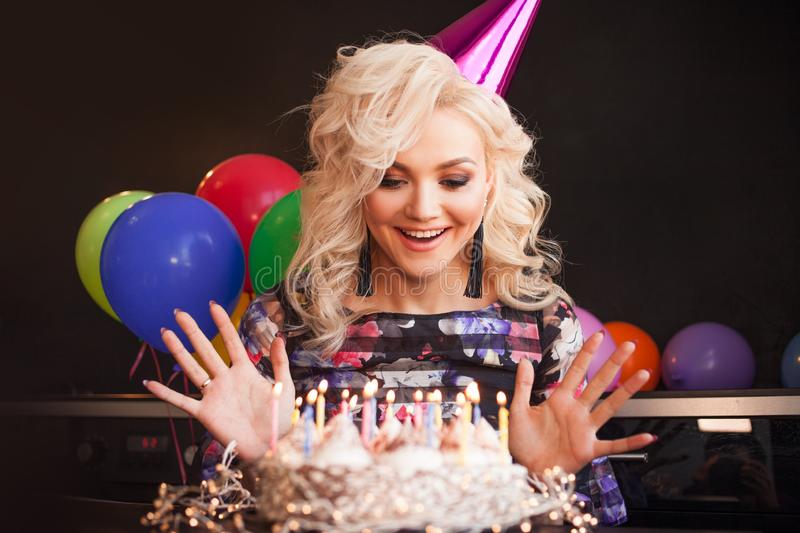 Birthday, a young woman blows out the candles on her birthday cake. stock images