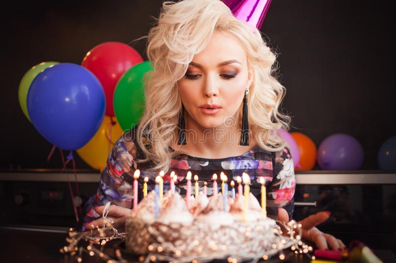Birthday, a young woman blows out the candles on her birthday cake. stock photos
